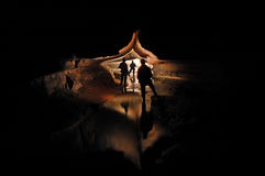 Spelunkers exploring an underground cave river. Spelunkers exploring a mystic cave river Royalty Free Stock Image