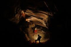 Spelunkers som undersöker en underjordisk grotta Arkivfoto