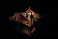 Spelunkers som undersöker en underjordisk grottaflod royaltyfri bild