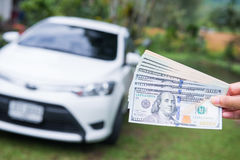 Spend money dollars to buy the car Stock Images
