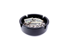Spend money by weird way. Ashtray filed tobacco ashes and burned-out money isolated over white Stock Photos