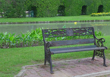 Spend relaxing time on a dark colored iron bench in public garden. Background Royalty Free Stock Photography