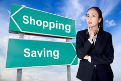 Spend save road sign with business woman thinking choice direction. The spend save road sign with business woman thinking choice direction Royalty Free Stock Image
