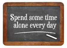 Spend some time alone every day. Inspirational words on a vintage slate blackboard Stock Photography