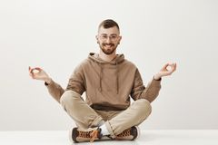 Spend some time to please your boyd. Charming full of life handsome guy sitting on floor with crossed legs, spreading. Hands, showing zen gesture, meditating Royalty Free Stock Image