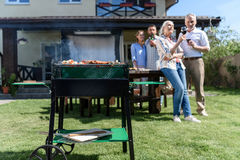 Spend time together while having barbecue with grill at yard Stock Photos