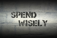 Spend wisely pr. Spend wisely stencil print on the grunge white brick wall Stock Photos