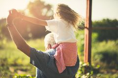 Spend your retirement days with your granddaughter. Grandfather and granddaughter spending time together in nature. Carrying on shoulders. Copy space royalty free stock photos
