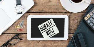 Spenden Sie jetzt auf Anmerkung über Telefon auf Schreibtisch mit Computer technol Lizenzfreie Stockfotos