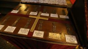 Spendenkasten in der Kirche mit verschiedenen Aufklebern, Ikone von heiliger Mary mit Kind beiseite stock video footage