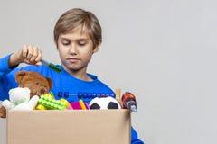 Spendenkonzept Kind, das Schulbedarf in Spendenkasten mit Kleidung, Spielwaren und Büchern sammelt stockbilder