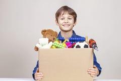 Spendenkonzept Kinderdas halten spenden Kasten mit Kleidung, Büchern, Schulbedarf und Spielwaren stockfoto