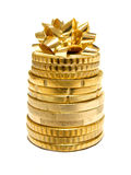 Spending. Holiday spending - a stack of coins with a gift bow on top on a white background Royalty Free Stock Images