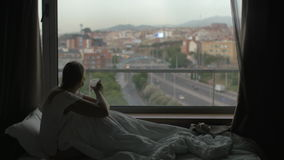 She spending all day in bed. Depressed woman having tea and looking at city while sitting under the blanket on bed stock video