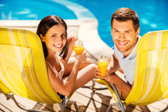 Spending carefree time poolside. Stock Image