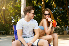 Spending carefree time poolside. Happy couple holding cocktails and smiling while sitting at the deck chairs by the pool Stock Photo