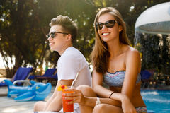 Spending carefree time poolside. Happy couple holding cocktails and smiling while sitting at the deck chairs by the pool.  Stock Photography