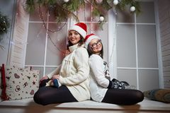 Happy mother and daughter sitting on a windowsill on Christmas e stock image