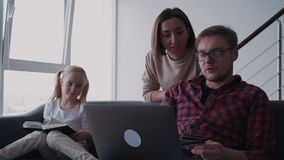 Family making online shopping while man holding computer and  ba. Spending free time at house together. Happy family sitting on sofa or couch in cozy and modern stock video