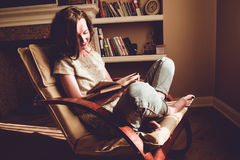 Spending free time by reading books. Home and comfort concept. Woman smiling reads interesting book in comfortable modern chair. N Stock Photography