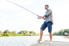 Spending good time fishing. Full length of confident young man fishing while standing on quayside Stock Image