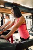 Spending great time at gym. Beautiful young cheerful girl in sportswear exercising on treadmill at gym with other girls stock photography