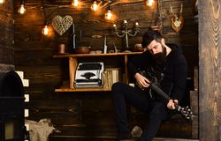 Spending great time at home. Man with beard holds black electric guitar. Guy in cozy warm atmosphere play music. Man. Bearded musician enjoy evening with bass royalty free stock images