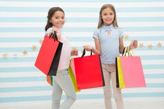 Spending great time together. Children satisfied shopping striped background. Obsessed with shopping and clothing malls. Discount concept. Kids cute girls hold royalty free stock image