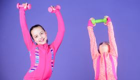Spending hours at gym. Cute sisters doing gym fitness exercises with dumbbells. Sport and fitness for kids. Little. Children developing physical fitness. Small royalty free stock image