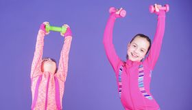 Spending hours at gym. Cute sisters doing gym fitness exercises with dumbbells. Sport and fitness for kids. Little. Children developing physical fitness. Small stock images