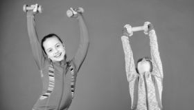 Spending hours at gym. Cute sisters doing gym fitness exercises with dumbbells. Sport and fitness for kids. Little. Children developing physical fitness. Small royalty free stock images