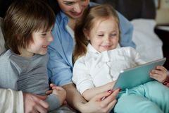 Spending leisure with kids. Young women and her kids watching videos in touchpad Royalty Free Stock Photos