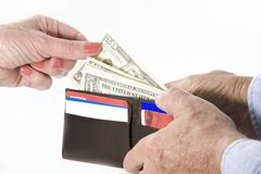 Spending Money. Image of a hand taking money from a working man's wallet over a white background stock photos