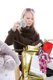 Spending money. Cute blond girl sitting on the floor with her shopping bags and counting money Stock Photos