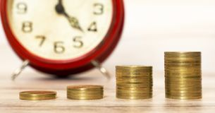 Spending money concept, coins with alarm clock in the background. Spending money concept, gold coins stack with an alarm clock in the background royalty free stock photography