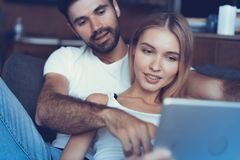 Spending nice time at home. Beautiful young loving couple bonding to each other and smiling while woman holding a book. Spending nice time at home. Beautiful stock photography