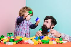 Spending nice time at home. building with colorful constructor. happy family leisure. father and son play game. love royalty free stock images