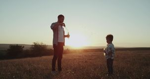 Spending a perfect time together dad and son at nature amazing sunset , making bubbles. stock video footage