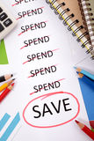 Spending plan and saving list circled. The word Save circled in red below a list of spending surrounded by pencils, graphs, books and calculator Stock Images