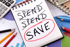 Saving money plan. The word Save circled in red below a list of spending written on a notepad surrounded by pencils, graphs, books and calculator Royalty Free Stock Photos