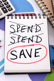 Saving plan checklist. The word Save circled in red below a list of spending written on a notepad surrounded by pencils, graphs, books and calculator Royalty Free Stock Photography