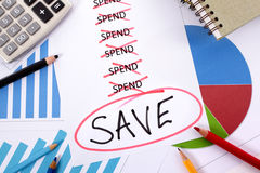 Saving money plan checklist. The word Save hand written and circled in red below a list of spending surrounded by pencils, graphs, books and calculator Stock Photo