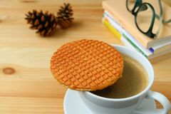 Spending Some Quiet Time with Stroopwafel and a Cup of Hot Coffee served on wooden table. Blurred Background Stock Photos