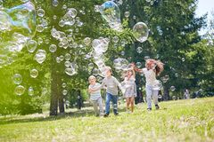 Spending Summer Day Outdoors. Group of cheerful little friends with wide smiles on their faces catching colorful soap bobbles while enjoying warm summer day Stock Photography