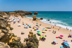 Spending summer holidays in seascape view on rocks cliffs with seas caves on sandy beach. Summer time royalty free stock images