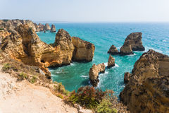 Spending summer holidays in seascape view on rocks cliffs with seas caves on sandy beach. Summer time stock photo