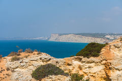 Spending summer holidays in seascape view on rocks cliffs with seas caves on sandy beach. Summer time stock image