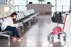 Spending time in airport lounge. With luggage hand-cart. One woman only Royalty Free Stock Image