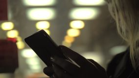 Spending time in the evening bus. Caucasian woman checking her cell phone whilst moving in a bus by the evening city stock video
