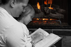 Spending time with Family. Father reads bedtime stories to his daughter in front of a glowing firelight